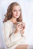 Kvinna som tycker om kaffe, medan koppla av hemma royaltyfria bilder