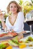 Kvinna som tycker om mål i utomhus- restaurang Arkivbilder