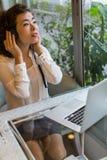 Kvinna som tycker om musik i hörlurar som sitter med en bärbar dator i ett kafé Arkivfoto