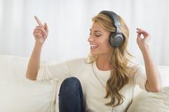 Kvinna som tycker om musik till och med hörlurar royaltyfria foton