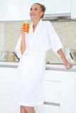 Kvinna som tycker om ny orange fruktsaft för frukost Royaltyfria Foton