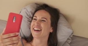 Kvinna som tycker om video pratstund genom att använda mobiltelefonen i säng stock video
