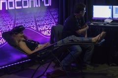 Kvinna som tycker om virtuell verklighetexponeringsglas, medan koppla av på soffan Arkivfoton