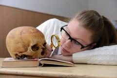 Kvinna som undersöker en mänsklig skalle Arkivfoto