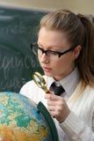 Kvinna som undersöker ett jordklot Arkivbilder