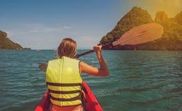 Kvinna som unders?ker den lugna tropiska fj?rden med kalkstenberg med kajaken royaltyfri fotografi