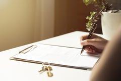 Kvinna som undertecknar ett avtalsdokument som gör ett fastighetköp arkivfoto