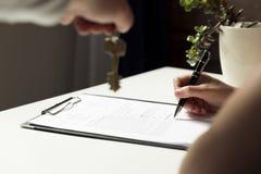 Kvinna som undertecknar ett avtalsdokument som gör ett fastighetköp royaltyfri foto