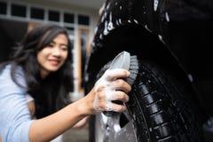 Kvinna som upp gör ren hennes bil arkivfoto