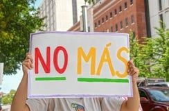 Kvinna som upp rymmer tecknet som säger ingen Mas - som är spansk för inga mer - framme av hennes framsida med högväxta byggnader royaltyfria bilder