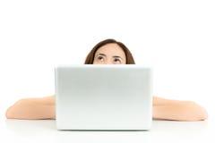 Kvinna som upp till ser kopieringsutrymme bakifrån hennes bärbar dator royaltyfria foton