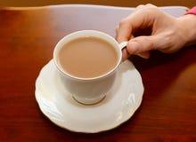 Kvinna som upp väljer en kopp te från en tabell Royaltyfri Foto