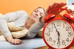 Kvinna som upp vaknar roterande av ringklockan i morgon Royaltyfri Bild