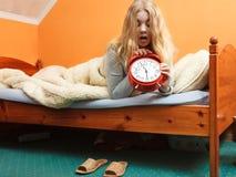 Kvinna som upp vaknar sent roterande av ringklockan Arkivfoto