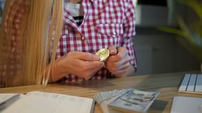 Kvinna som uppmärksamt ser på bitcoin i händer Kantjustera sikten av den blonda kvinnlign i rutigt tillfälligt skjortasammanträde lager videofilmer