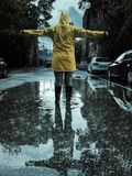 Kvinna som ut når hennes armar på en regnig dag i höst arkivbild