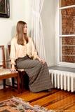 Kvinna som ut ser fönsterslotten Arkivbild