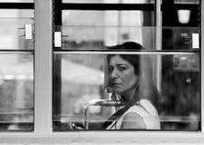 Kvinna som ut ser fönstret för spårvagn` s Royaltyfria Foton