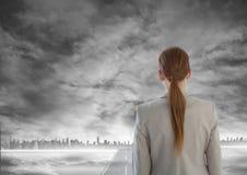 Kvinna som ut ser på grå stadshorisont med vägen som leder till staden under rök Royaltyfri Bild