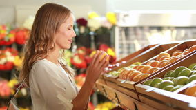 Kvinna som ut väljer frukt i supermarket arkivfilmer