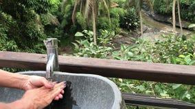 Kvinna som utanför tvättar henne händer med en härlig tropisk sikt Friskhet- och ekologibegrepp Bali ö arkivfilmer