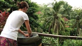 Kvinna som utanför tvättar henne händer med en härlig tropisk sikt Friskhet- och ekologibegrepp Bali ö stock video