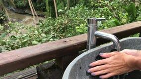Kvinna som utanför tvättar henne händer med en härlig tropisk sikt Friskhet- och ekologibegrepp Bali ö lager videofilmer