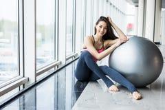 Kvinna som utarbetar med övningsbollen i idrottshall Pilates kvinna som gör övningar i idrottshallgenomkörarerummet med kondition fotografering för bildbyråer