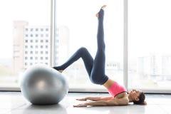Kvinna som utarbetar med övningsbollen i idrottshall Pilates kvinna som gör övningar i idrottshallgenomkörarerummet med kondition Royaltyfri Foto