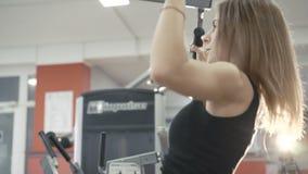 Kvinna som utarbetar med simulatorn för muskler på armar och baksida i idrottshallen i 4k lager videofilmer