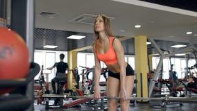 Kvinna som utarbetar på en idrottshall med övningsutrustning stock video