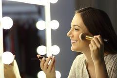 Kvinna som utgör genom att använda en borste Arkivfoto
