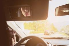 Kvinna som utgör hennes framsida genom att använda läppstift, medan köra bilen arkivfoton
