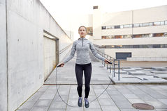 Kvinna som utomhus övar med hopp-repet Royaltyfria Bilder