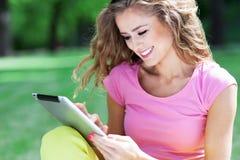 Kvinna som utomhus använder den digitala minnestavlan Royaltyfri Foto