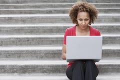 Kvinna som utomhus använder bärbara datorn på moment Arkivfoton