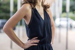 Kvinna som utomhus bär en svart sommarklänning på en neutral stadsbakgrund royaltyfri bild