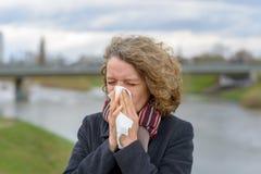 Kvinna som utomhus blåser hennes näsa på ett silkespapper royaltyfria bilder