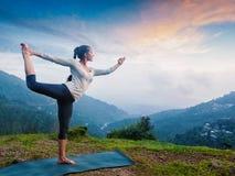 Kvinna som utomhus gör yogaasanaen Natarajasana på vattenfallet Royaltyfria Bilder
