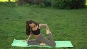 Kvinna som utomhus lär yoga själv vid smartphonen stock video