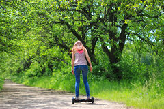 Kvinna som utomhus rider en elektrisk sparkcykel Arkivbild