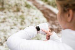 Kvinna som utomhus utarbetar och kontrollerar hennes digitala klocka Royaltyfri Bild