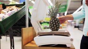Kvinna som väger ananas på skala på livsmedelsbutiken stock video