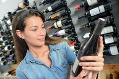 Kvinna som väljer flaskvin arkivfoto