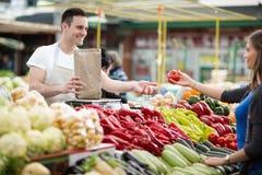Kvinna som väljer grönsaker för att mäta i livsmedelsbutik royaltyfri foto