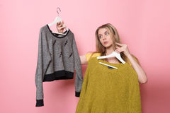 Kvinna som väljer hennes modedräkt Flicka som tänker vad för att bära efter shoppingen arkivfoton