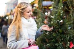 Kvinna som väljer julgranen Arkivfoto