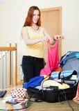 Kvinna som väljer kläder för semester Arkivbilder