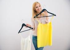 Kvinna som väljer klänningen Arkivbild