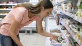 Kvinna som väljer mejeriprodukter i kyl på livsmedelsbutikavdelningen av shoppinggallerian royaltyfri fotografi